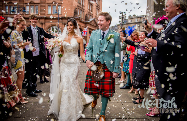 Bride, groom and confetti in Edinburgh wedding.