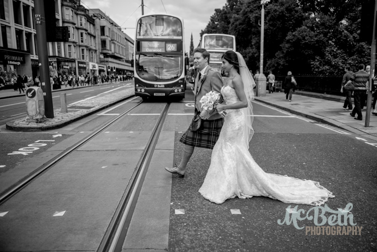 Bride and groom crossing Princes street in Edinburgh