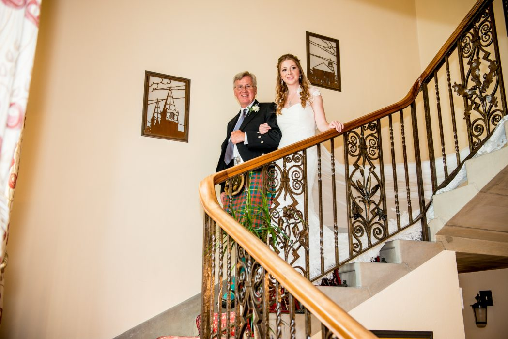 Dad leads bride down the stairs.